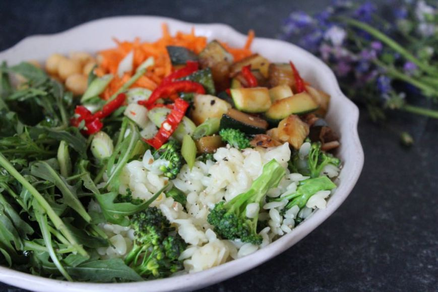 Buddha Bowl with boiled rice, rocket, broccoli, courgette, grated carrot and chickpeas, topped with spring onions and chilli slices.