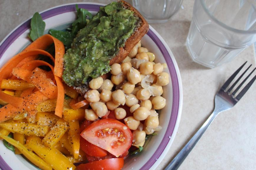 Buddha Bowl with Carrot Ribbons, Pepper Slices, Tomato Quarters, Chickpeas, Rocket and Smashed Avocado on Homemade Brown Bread.