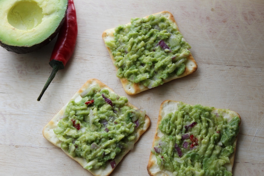 Guacamole. Smashed avocado with red onion and red chilli and lemon juice on crackers.