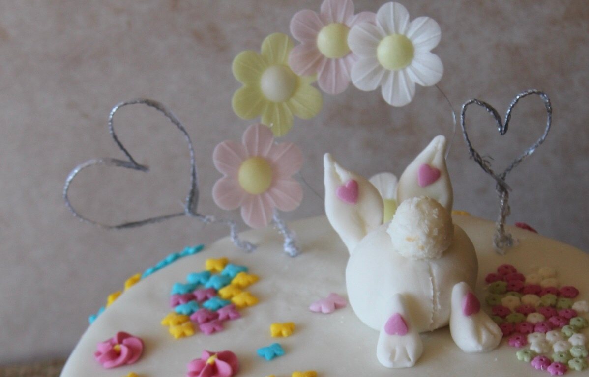 Easter Simnel Cake 2020 decorated with fondant icing and Easter decorations including bunny, flowers and butterflies.