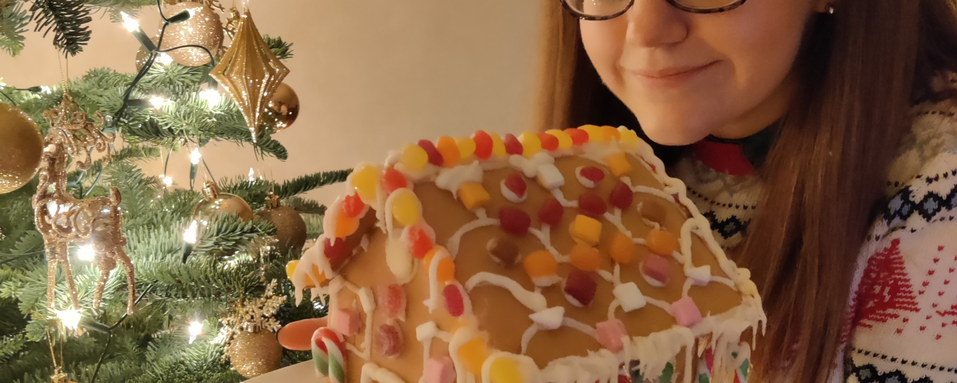 Girl holding a decorated gingerbread house in front of a lit Christmas tree.