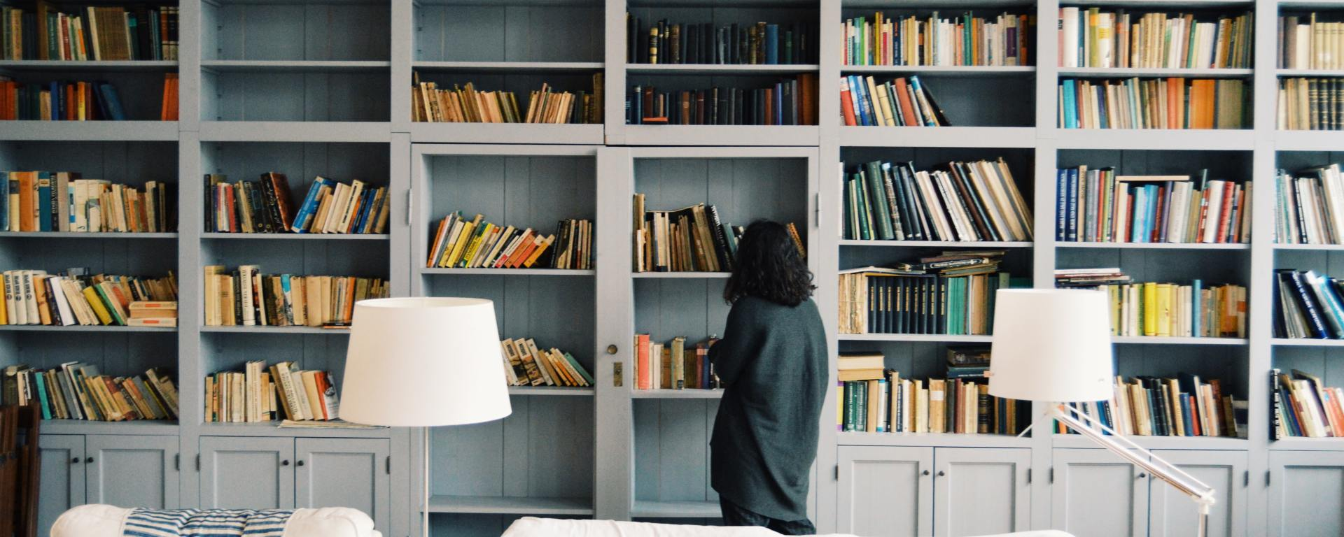 Girl looking at books on a book shelf